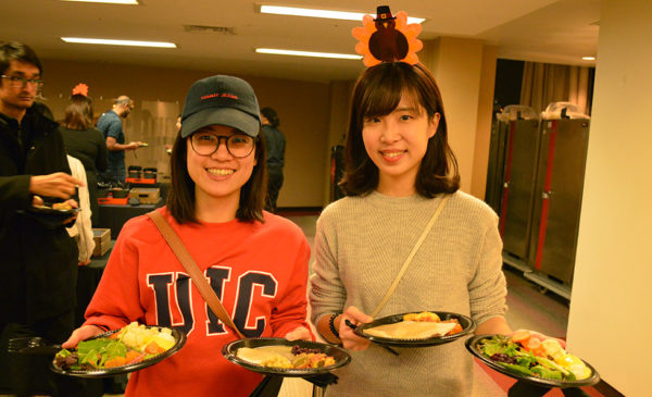 International students hold plates of Thanksgiving food.