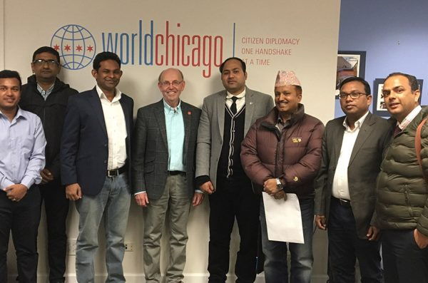 Eight men, inlcuding UIC Professor Dr. Evan McKenzie and senior delegates from India, Bangladesh, Nepal and Sri Lanka, pose and smile for a photo in front of a wall with the logo of Work Chicago.