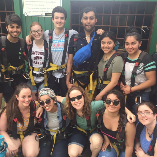 Fourteen UIC students posing smiling and wearing climbing gear in St Kitts.