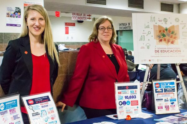 Two women dressed in red and blue and wearing UIC pins stand behind a table displaying UIC informational handouts.