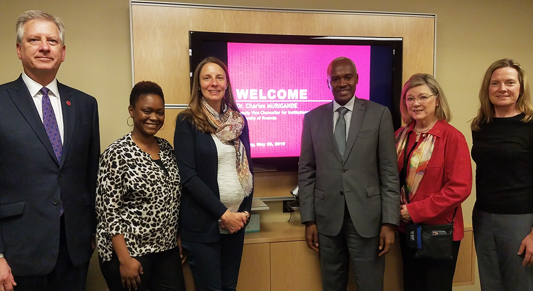 Five UIC faculty members stand with Ambassador Charles Murigande in front of a screen projecting the words