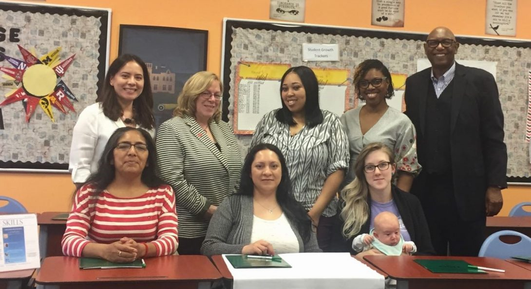 Seven women and one man pose together in a classroom. Three of the women are sitting at a table with a banner hanging off of it that says