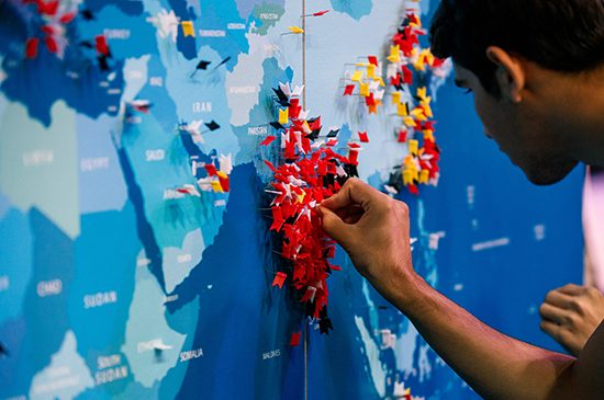 A UIC student pressing a colored pin into a map of the world.