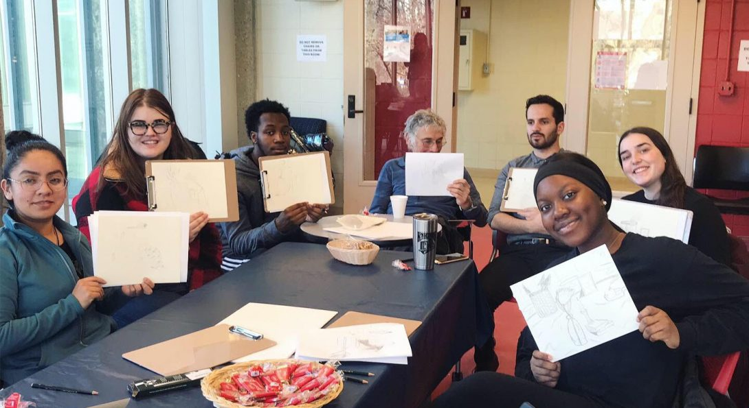 Seven students and faculty sitting holding up pieces of art they sketched